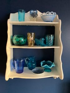 collection of blue glass objects on shelf